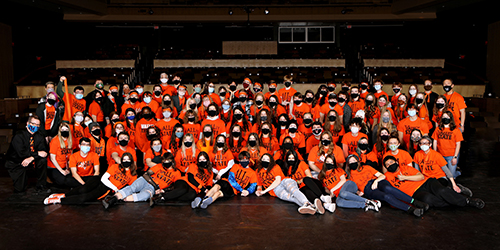 WDMCS' IHSSA Large Group All-State students on stage together in matching orange shirts.